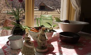 collectibles on a kitchen table with a view of the barn through the window
